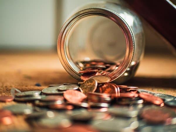 硬貨が瓶からこぼれる画像